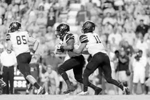 Junior quarterback Taylor Lamb passes the ball to senior running back Marcus Cox.