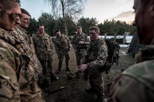 Soldiers stand in a circle getting a debrief after an exercise