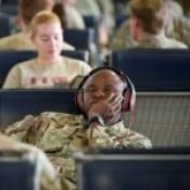 A soldier in an airport listens to Podcasts on his headphones