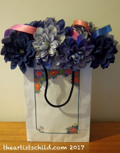 60s flower power party decoration, recycled fabric flowers from op shop and ribbon, white paper shopping bag with attached vintage note paper