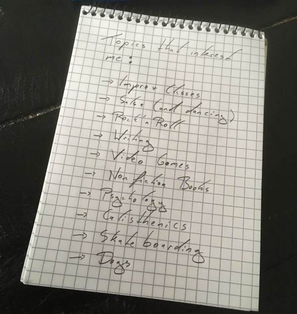 list of interests for friend cirlce written on a note pad. interests include improv, salsa dancing, rock n' roll, writing, video games, psychology, and calisthenics.