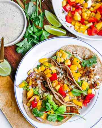 These fish tacos with mango salsa and creamy white lightning sauce are full of vibrant flavours layered together to create a perfect bite. Made with baked fish and lots of fresh ingredients, they're healthy but they taste like pure indulgence. All for only 400 calories and 10 grams of fat per serving of 3. The best part is that they're quick and easy to make. Fish tacos are the answer to boring weeknight meals.