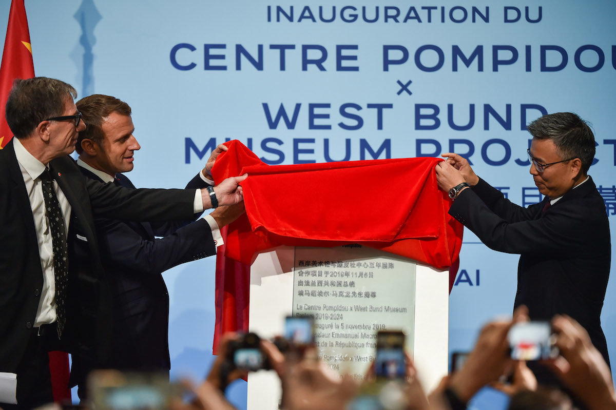 French President Emmanuel Macron (C), president of Centre Pompidou Serge Lasvignes (L), and Fong Shizhong (R) unveil a plaque during the inauguration of the Centre Pompidou West Bund Museum in Shanghai. Photo by Hector Retamal/POOL/AFP via Getty Images.