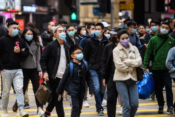 Pedestrians wearing face masks cross a road during a Lunar New Year of the Rat public holiday in Hong Kong on January 27, 2020. Photo by Anthony Wallace/AFP via Getty Images.