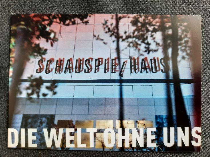 """Eine Werbepostkarte, die für das Theaterstück """"Die Welt ohne uns"""" wirbt. Zu sehen ist eine blau beleuchtet, glatte Hausfassade, auf der das Wort """"Schauspielhaus"""" angebracht ist. Im Vordergrund sind mehrere Bäume als unscharfer Schattenriss zu erkennen."""