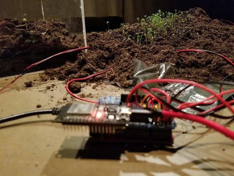 Ein technisches Gerät, aus dem rote Kabel quellen steht auf eine, braunen Tisch. Dahinter ist ein Haufen Erde auf dem Tisch zu sehen, auf dem kleine Pflanzen wachsen.