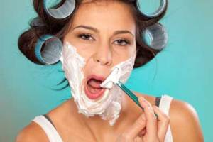 woman with large curlers shaving her face