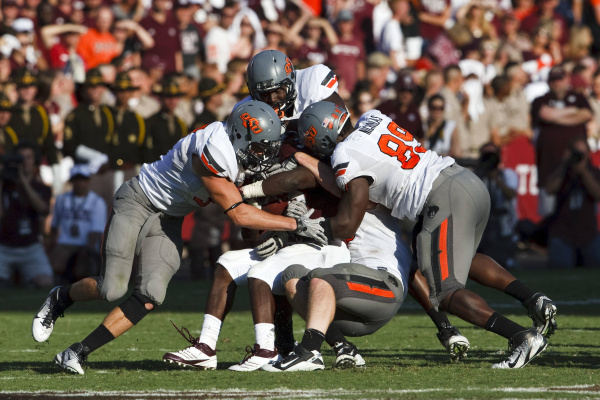 Members of the 2011 Oklahoma State Cowboys defense swallow up a would-be scrambling quarterback during a game