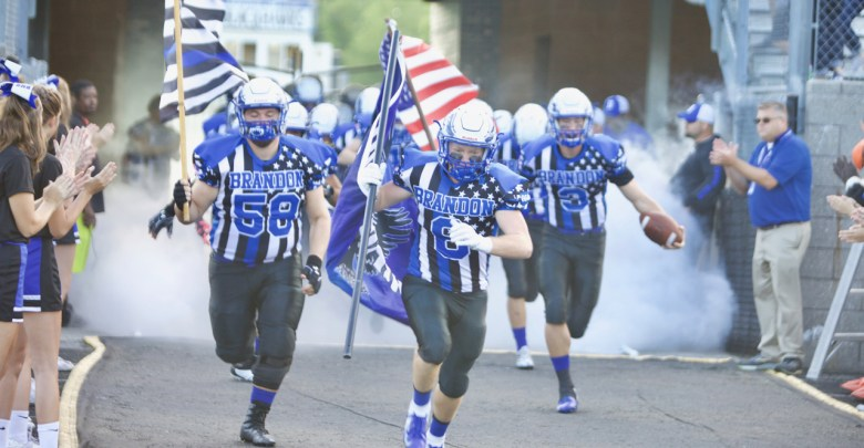 Brandon Blackhawks team captains Jake Irwin (#8), Matt Hill (#58), and Mathew Harrison (#3) lead the team out of the tunnel before their First Responders Game against cross town rival Goodrich Martians.