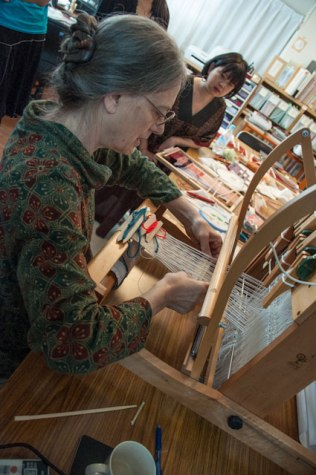 Monica Bethe demonstrating techiniques on a small loom