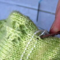 Starting from the right, with a needle one size smaller than these used to knit the sock, pick up the right leg of the stitches as you come to them. Simply follow the lifeline, and insert the needle where the lifeline goes.