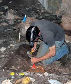 Ken Aplin (CSIRO) hammering through the solidified cave floor using a large chisel.