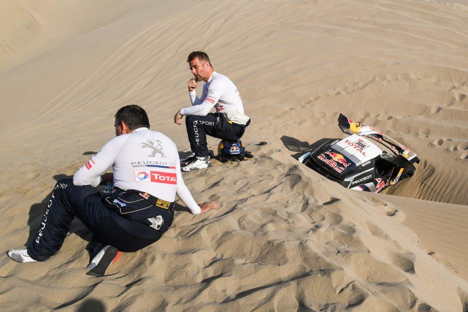Sebastien Loeb et Daniel Elena et la 3008DKR tankée en bas d'une dune de sable