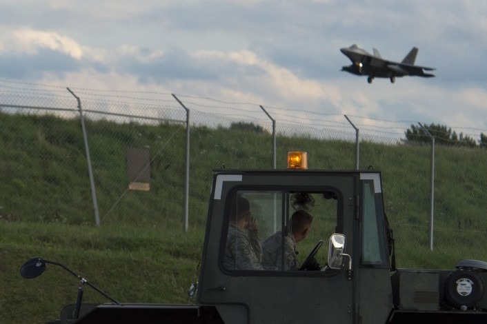 Two Airmen watch as an F-22 Raptor fighter aircraft assigned to the 95th Fighter Squadron at Tyndall Air Force Base, Fla., prepares to land at Spangdahlem Air Base, Germany, Aug. 28, 2015. The U.S. Air Force deployed four F-22s, one C-17 Globemaster III and more than 50 Airmen to Spangdahlem in support of the first F-22 European training deployment. The inaugural F-22 training deployment to Europe is funded by the European Reassurance Initiative, a $1 billion pledge announced by President Obama in March 2014. (U.S. Air Force photo by Airman 1st Class Luke Kitterman/Released)