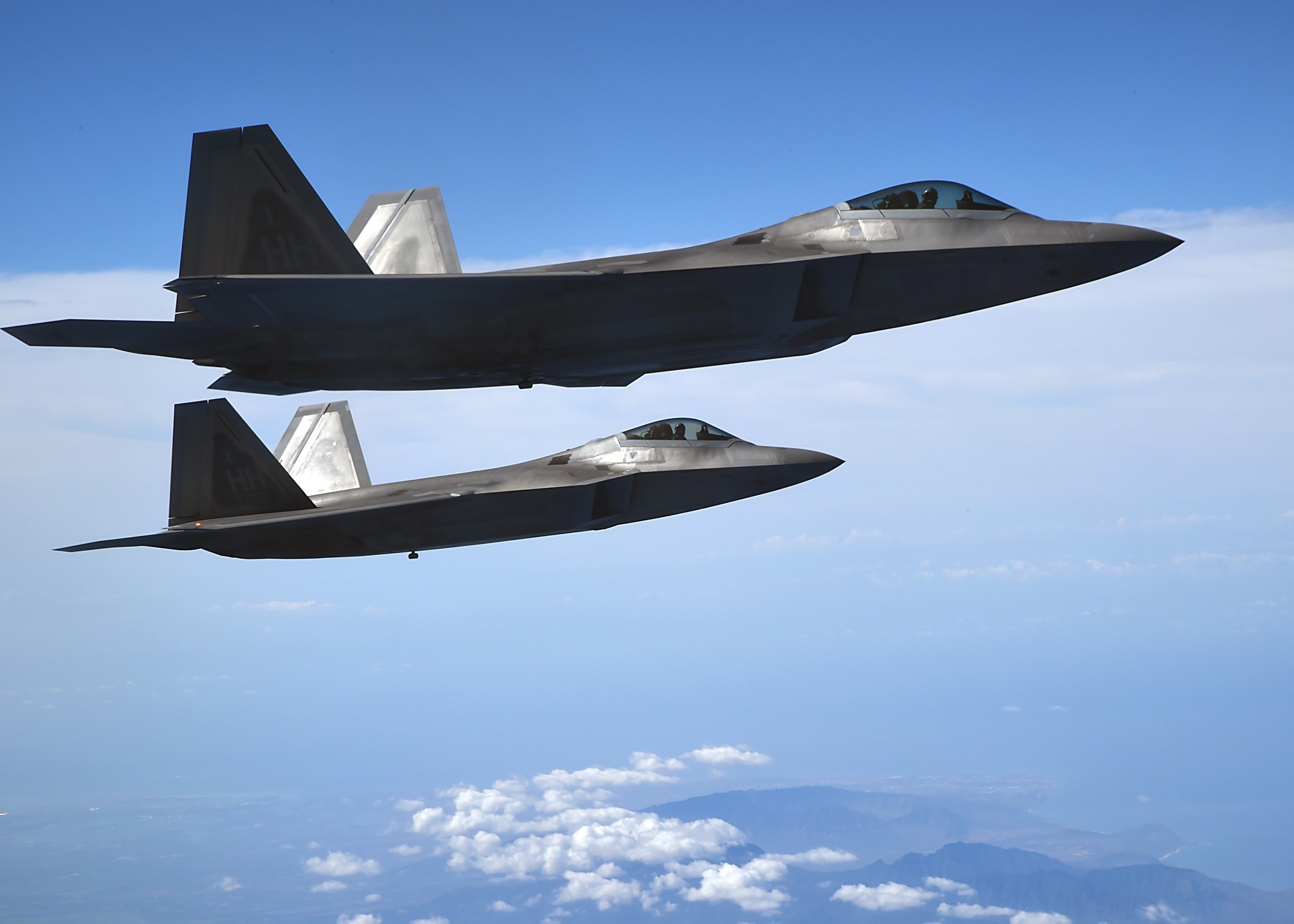 United States Air Force F-22 Raptors, from the Hawaiian Raptors, fly in formation above the island of Oahu, Hawaii, May 19, 2015. The F-22 pilots conducted aerial refueling operations with the 96th Air Refueling Squadron's KC-135R Stratotanker. The F-22 Raptor is a fighter aircraft that combines stealth, supercruise, maneuverability, and integrated avionics, coupled with improved supportability, to represent an exponential leap in warfighting capabilities. (U.S. Air Force photo by Tech. Sgt. Aaron Oelrich/Released)