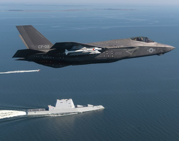 "An F-35 Lightning II Carrier Variant (CV) piloted by U.S. Marine Corps Maj. Robert ""Champ"" Guyette II, a test pilot from the F-35 Pax River Integrated Test Force (ITF) assigned to the Salty Dogs of Air Test and Evaluation Squadron (VX) 23, flies over the stealth guided-missile destroyer USS Zumwalt (DDG 1000) as the ship transits the Chesapeake Bay on Oct. 17, 2016. USS Zumwalt, the Navy's newest and most technologically advanced surface ship, joined the fleet Oct. 15. The F-35C Lightning II — a next generation single-seat, single-engine strike fighter that incorporates stealth technologies, defensive avionics, internal and external weapons, and a revolutionary sensor fusion capability — is designed as the U.S. Navy's first-day-of-war, survivable strike fighter. The U.S. Navy anticipates declaring the F-35C combat-ready in 2018. (U.S. Navy photo by Andy Wolfe/Released)"