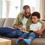 A father is reading to his son on the couch