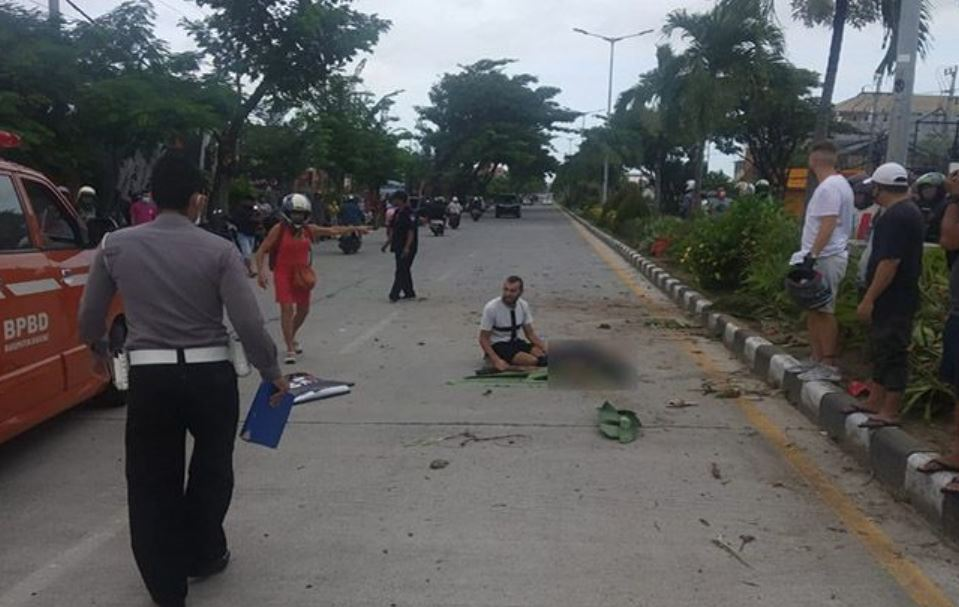 man sitting next to victim on sunset road in bali