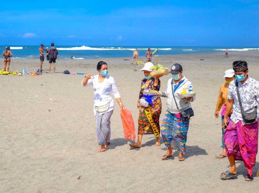 bali residents on beach wearing masks