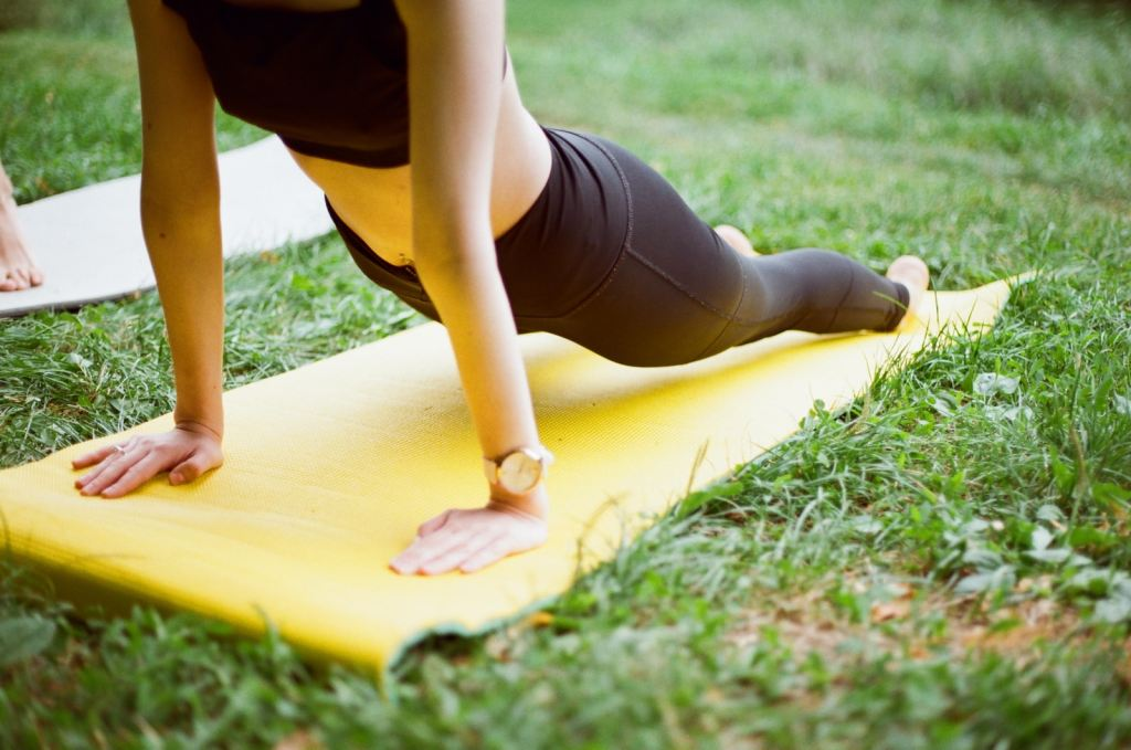 Outdoor Events; Woman In Black Shorts And Black Stockings Lying On Yellow Surfboard