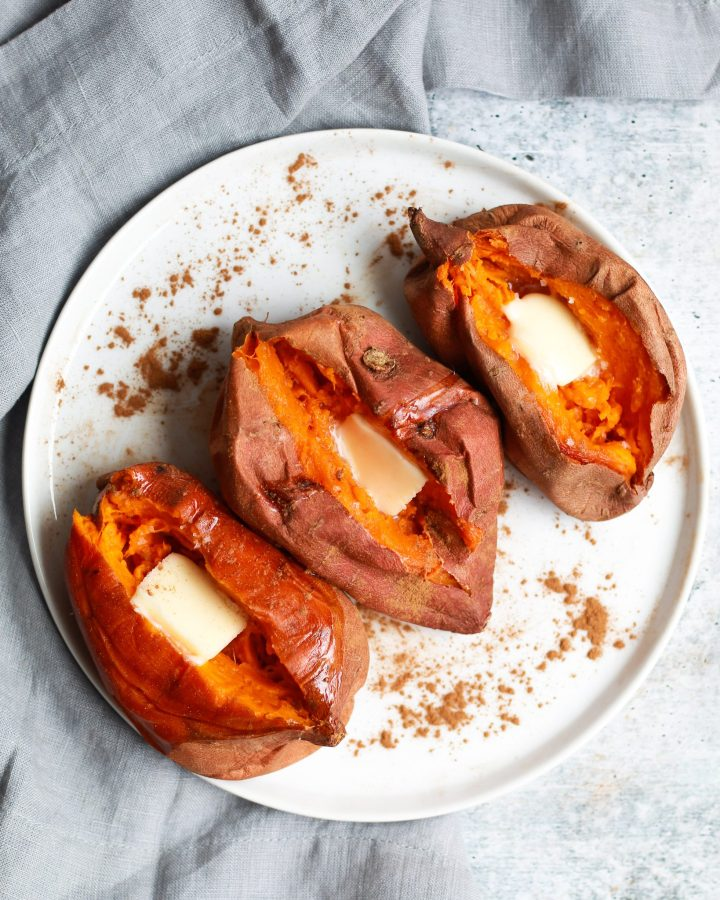 side view of three baked sweet potatoes with a pat of butter