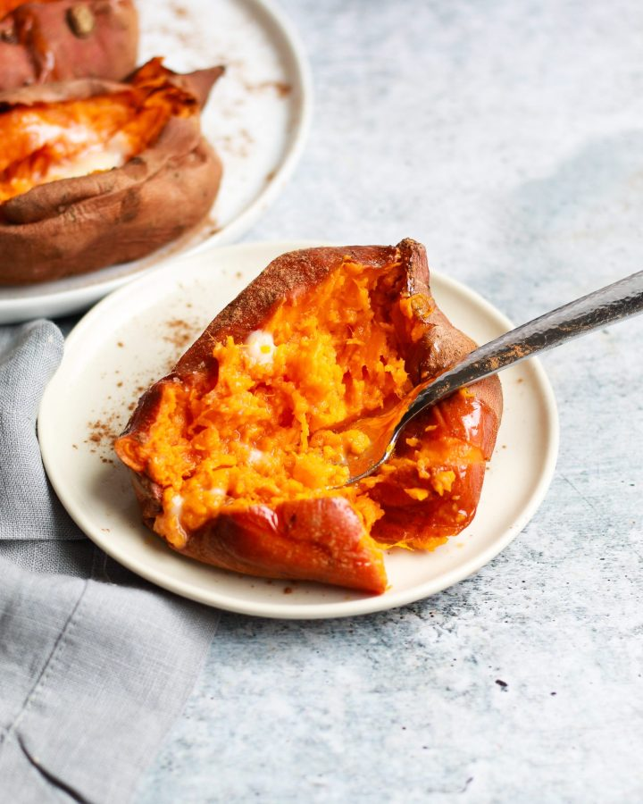 mashed baked sweet potato with pat of butter on a small plate with a fork in it
