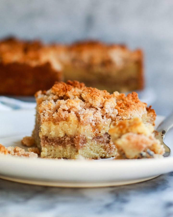 up close photo of slice of cinnamon coffee cake with a bite out of it