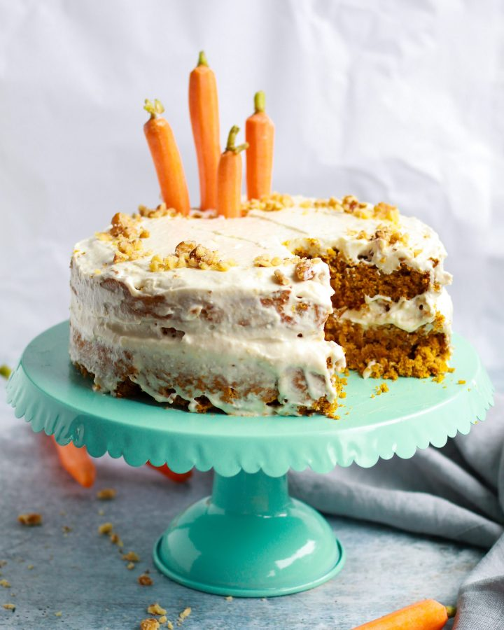 vegan carrot cake on stand with slice out of it