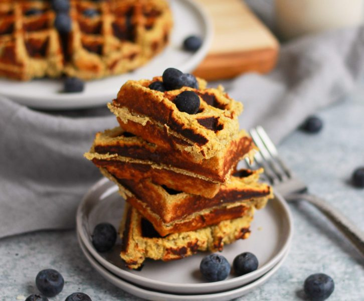 close up of paleo sweet potato waffles with blueberries and maple syrup