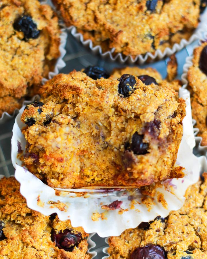 close up of vegan blueberry muffin, one with a bite