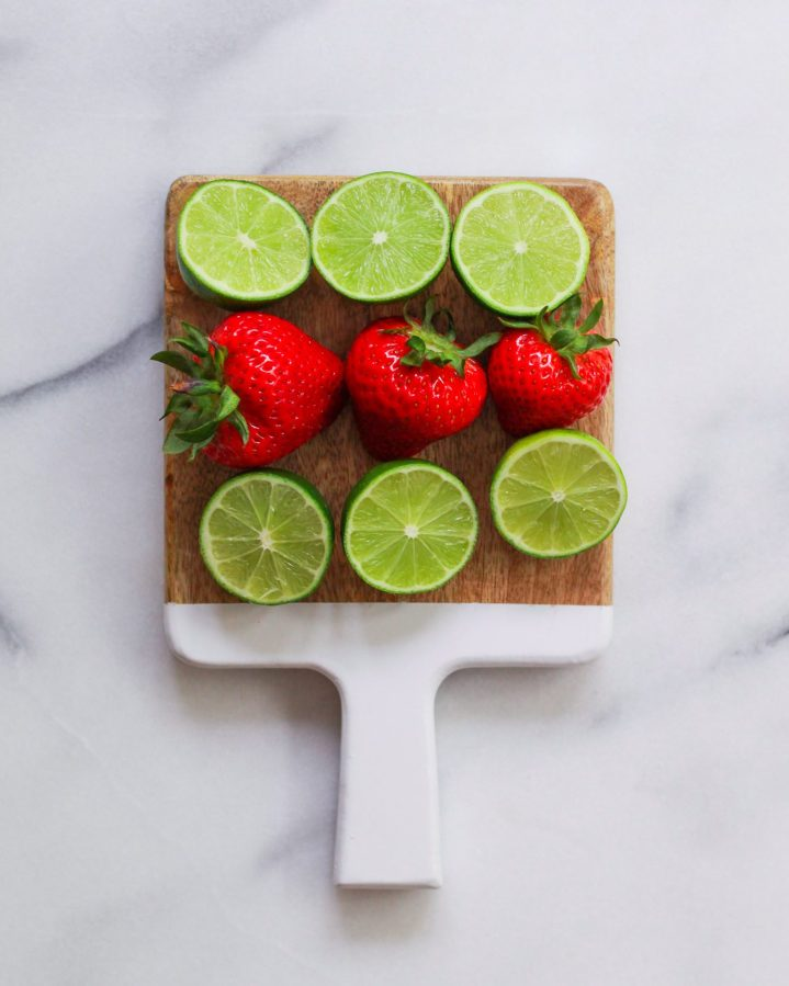 strawberries and limes on a cutting board
