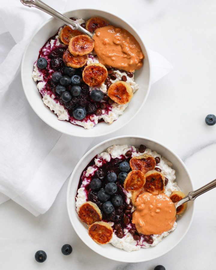 two oatmeal bowls in white bowls with banana, blueberries, and peanut butter