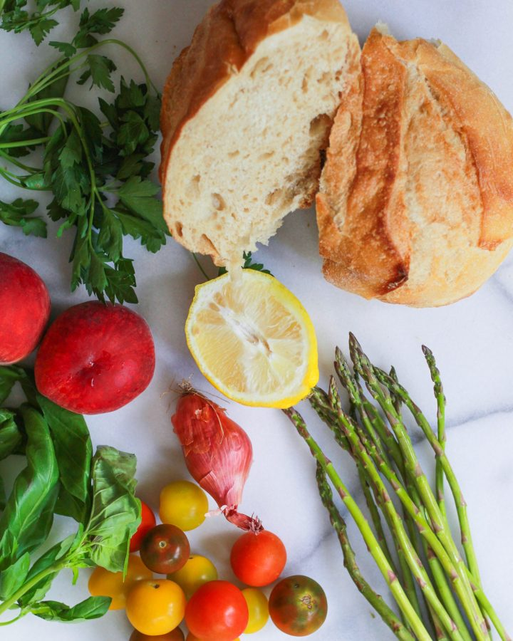 loaf of bread with peaches, asparagus, shallots, heirloom tomatoes, basil, and parsley