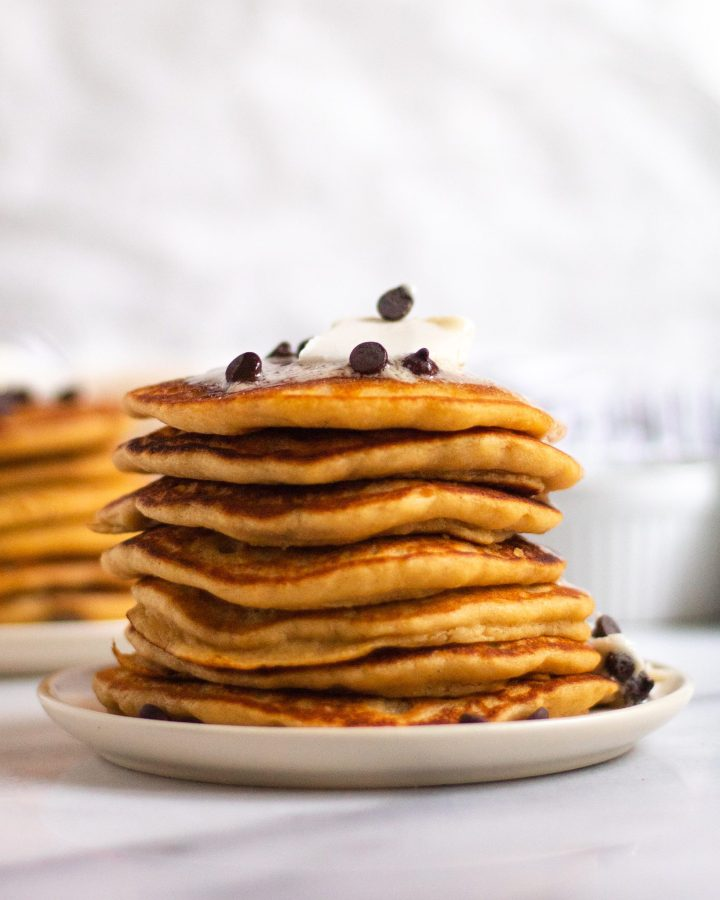 stack of fluffy vegan buttermilk pancakes with chocolate chips and vegan butter on a white plate