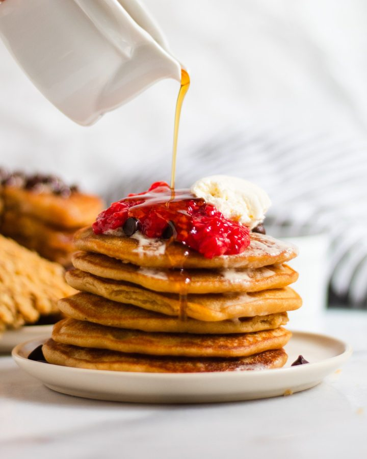 drizzle of maple syrup on raspberry pancakes