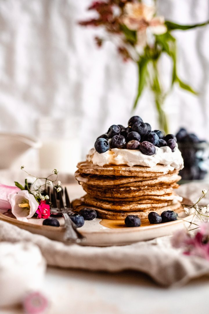 stack of healthy vegan pancakes with coconut whipped cream and blueberries