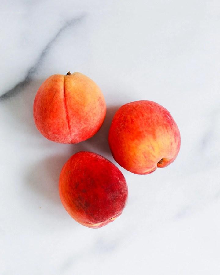 three peaches on marble slab