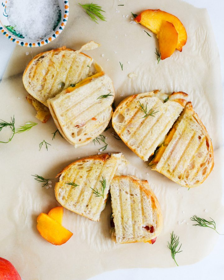 three peach grilled cheese sandwiches on parchment paper