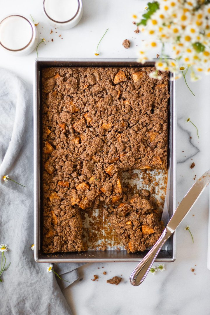slice of apple crumb cake in cake pan with two glasses of almond milk