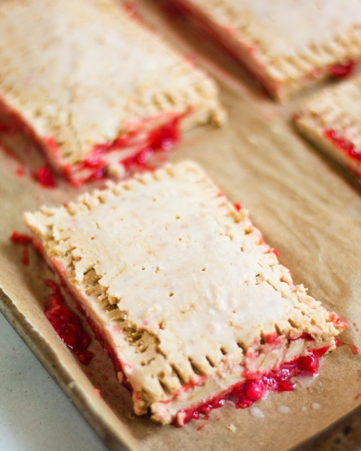 unbaked raspberry pop tarts on a baking sheet
