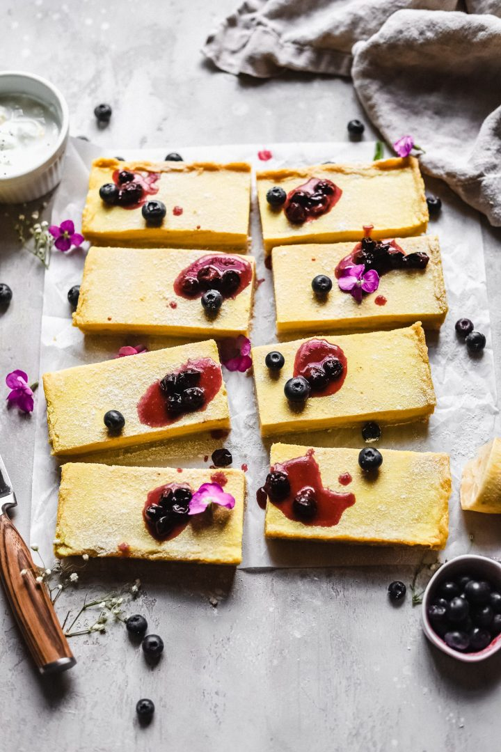 3/4 shot of lemon bars with blueberries and warmed blueberry jam on top