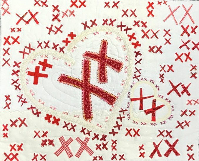 white cloth embellished with pairs of red X's that are all different sizes and shades of red