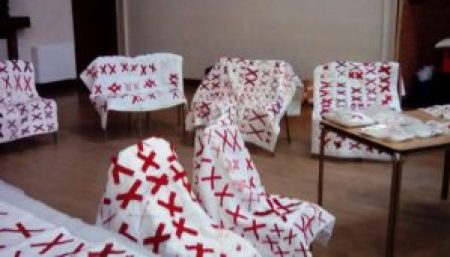 quilts made of white bases covered with pairs of red X's are draped over chairs and tables at Coxhoe Village Hall in the U.K.