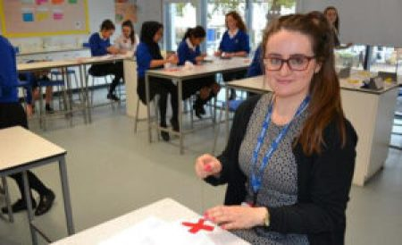A female wearing glasses and a black sweater sews two red X's onto a white base to make a block for The 70273 Project