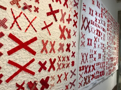 wall filled with quilts made of pairs of red X's stitched onto white background fabric