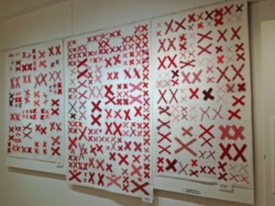 White quilts covered with pairs of red X's on display in a museum