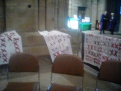 quilts made of pairs of red X's sewn onto white background fabric are on display at Durham Cathedral in the U.K.