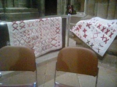 quilts made of pairs of red X's sewn onto a white background are on display at Durham Cathedral in the U.K.