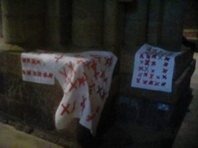 quilts made of pairs of red X's sewn onto a white background are draped over pews in Durham Cathedral in the U.K.