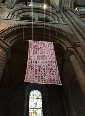 a quilt made of pairs of red x's sewn onto a white background hands in Durham Cathedral